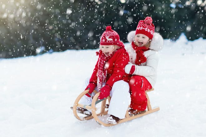 Two little girls sledging in the snow