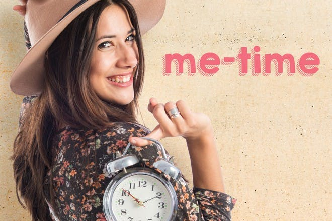 woman holding clock over shoulder
