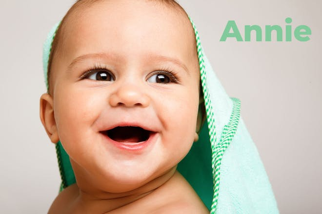 Baby wearing green hooded towel. Name Annie written in text