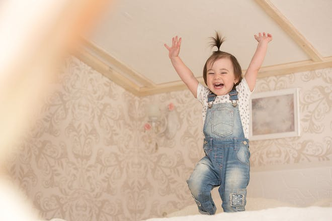 toddler jumping on bed