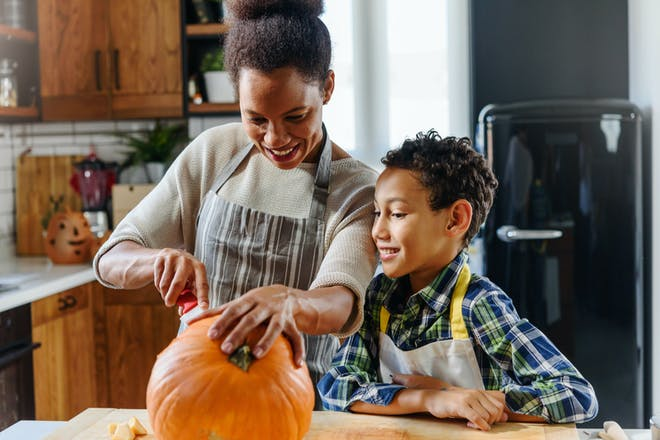 Mother and son carving a pumpkin together in the kitchen