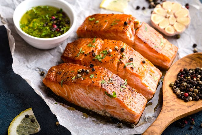 three cooked salmon steaks with peppercorns