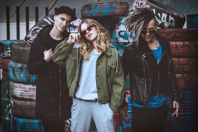 Group of edgy teens with punky hair, leather jackets, standing in front of graffiti