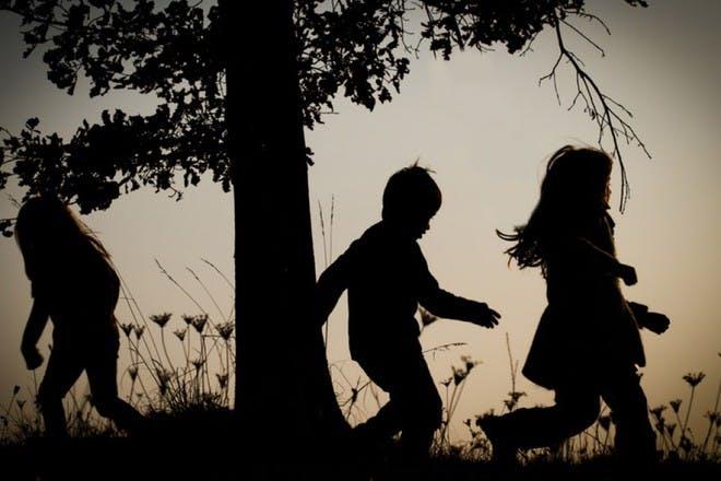 children running through trees at sundown