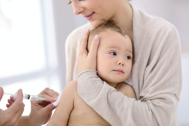 A baby being held by its mother as it receives a vaccination injection