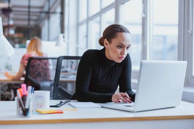 woman sitting at desk in office working on computer