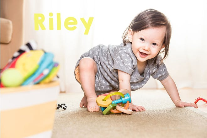 Baby playing with toys. Text says Riley