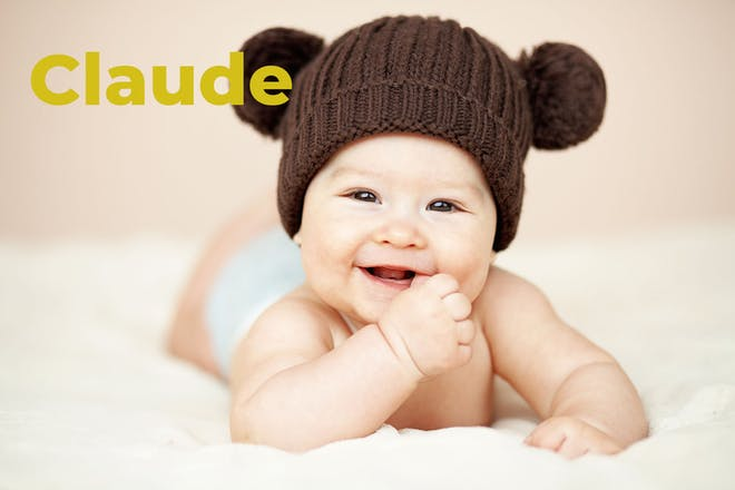 Baby wearing brown wool hat with pom poms for ears. Name Claude written in text