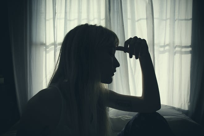 Silhouette of woman looking out of window