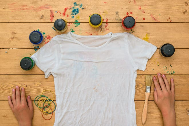 Plain white T-shirt surrounded by elastic bands and fabric dye