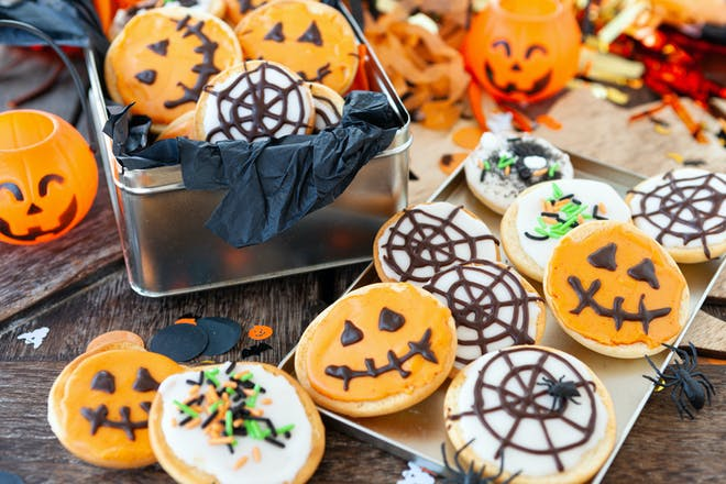 Spiced biscuits decorated with pumpkin and spider web icing for Halloween