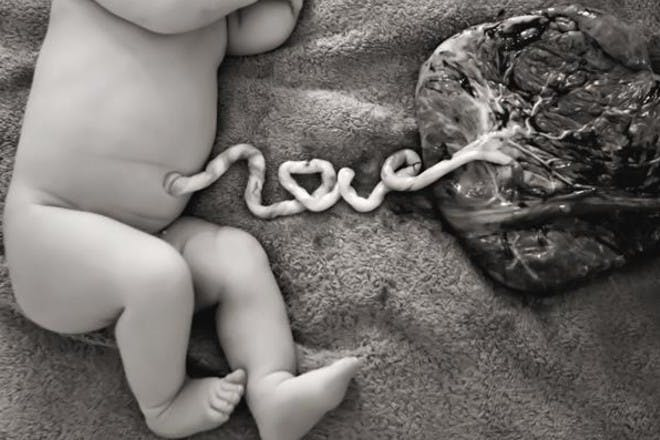 black and white of newborn lying on blanket with umbilical cord and after birth still attached