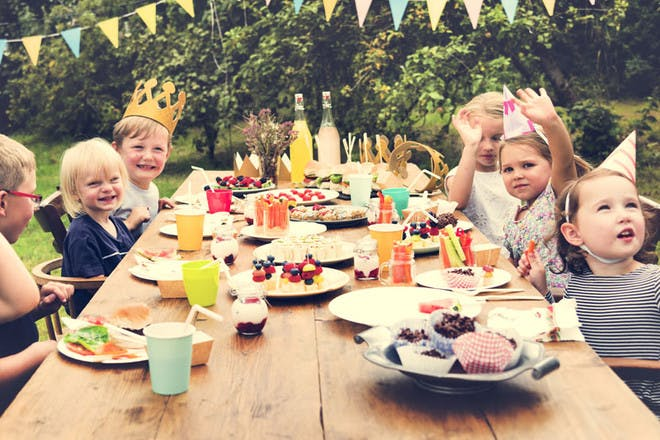 Outdoor picnic birthday party with children sat at a wooden table, wearing party hats