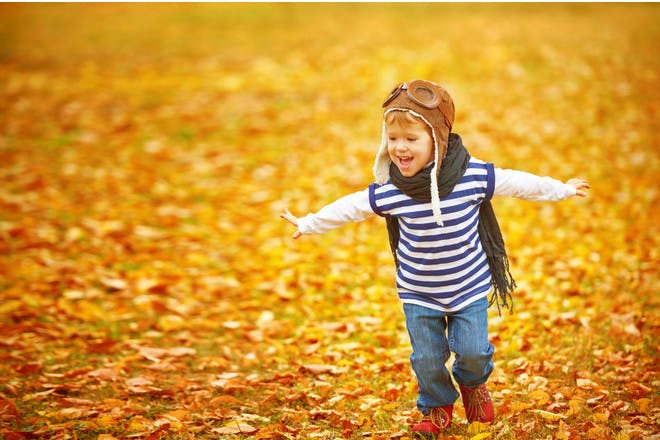 boy pretending to be aeroplane in autumn leaves