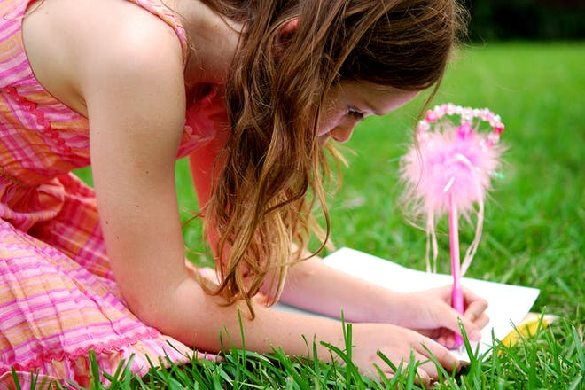 Girl writing in notebook with fluffy pen