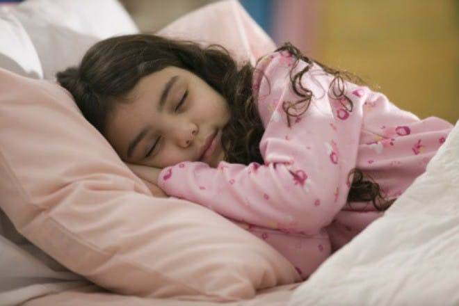 girl in pink sleeping in bed