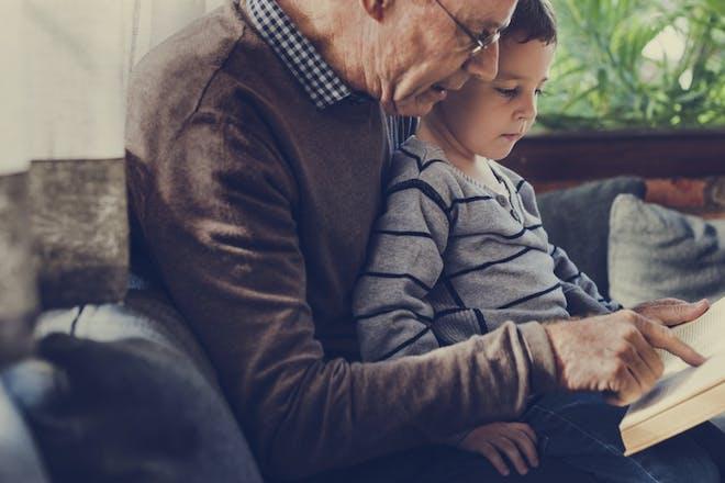 Grandad and grandson reading together
