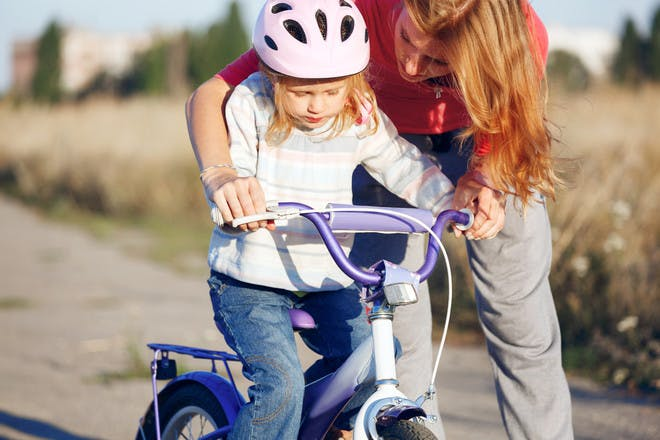 little girl learning to ride a bike