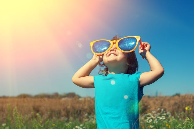 Child with big sunglasses looking at sun