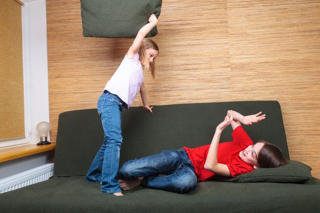 brother and sister fighting on sofa