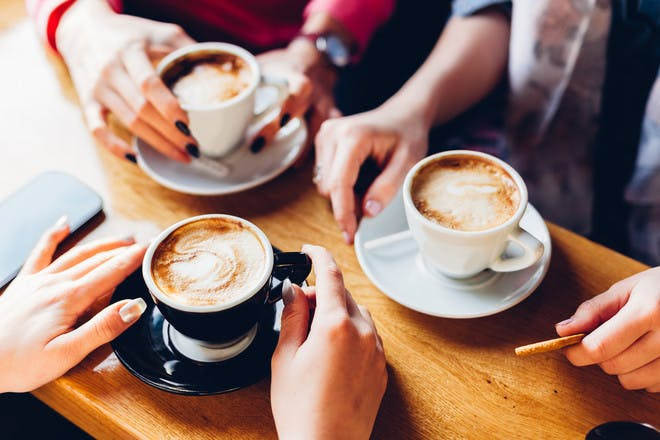 Group of hands holding coffees
