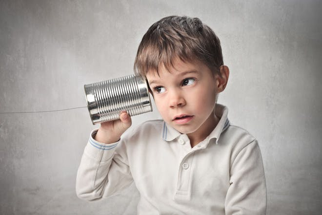 Boy listening through tin can