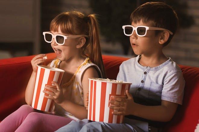 Two kids enjoying a movie night with popcorn