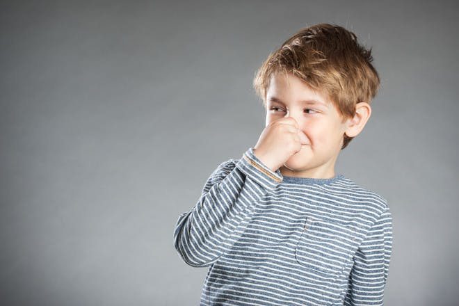 Child holding their nose