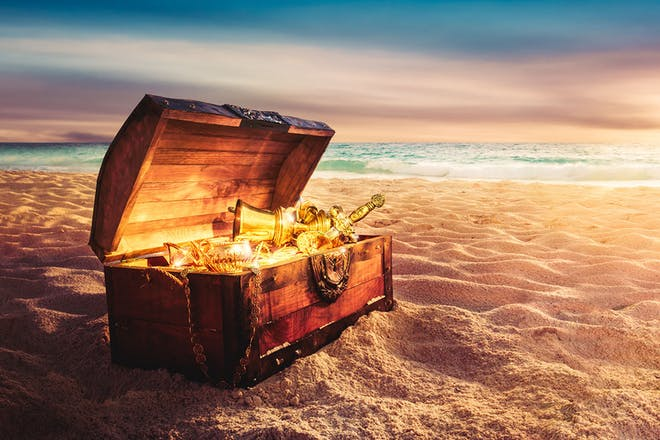 Chest of gold loot on a beach