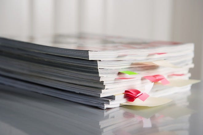 pile of magazines with colourful page markers sticking out from them