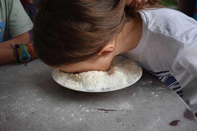 Girl with face in plate of flour as part of party game
