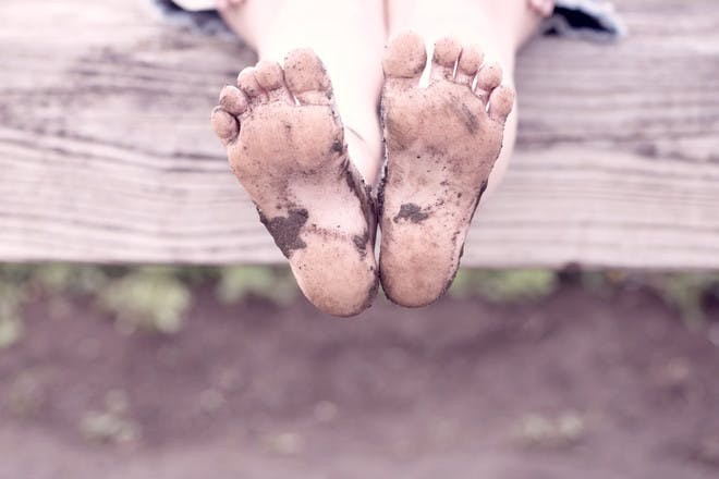 Child with muddy feet on wild camping trip