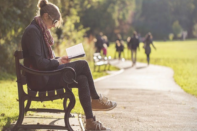 woman sitting on park bench reading book