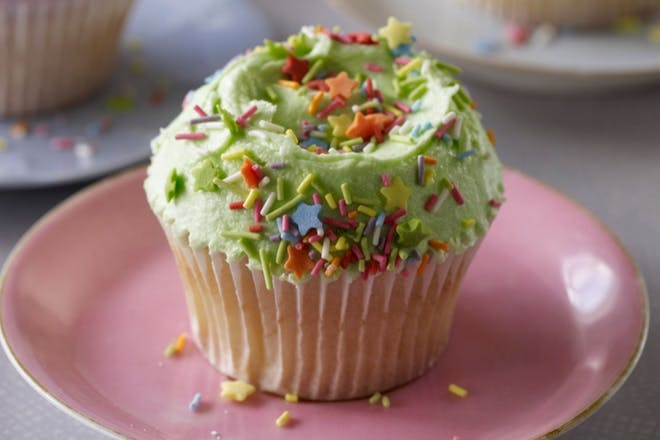 A vanilla cupcake with green frosting and sprinkles