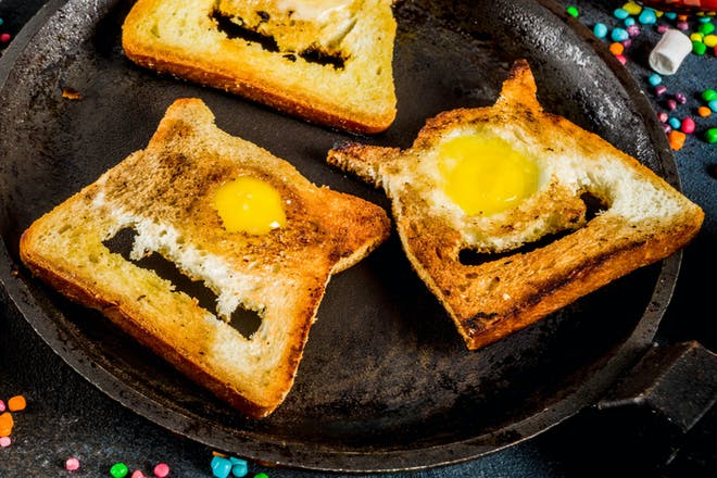 Toast cut to look like Halloween monster with toothy smile and egg yolk eye