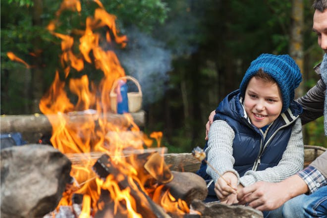 Boy with campfire in the woods