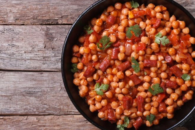 Vegan chickpea stew with tomatoes and peppers in a blackpan