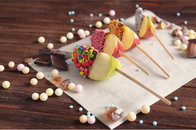 Apple slices coated in chocolate, toffee and cake sprinkles served on lollipop sticks for Halloween