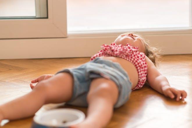 young girl lying on floor having tantrum