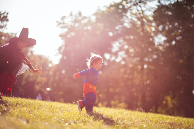 A little girl dressed as a witch chases a toddler dressed in a Superman costume through a park.