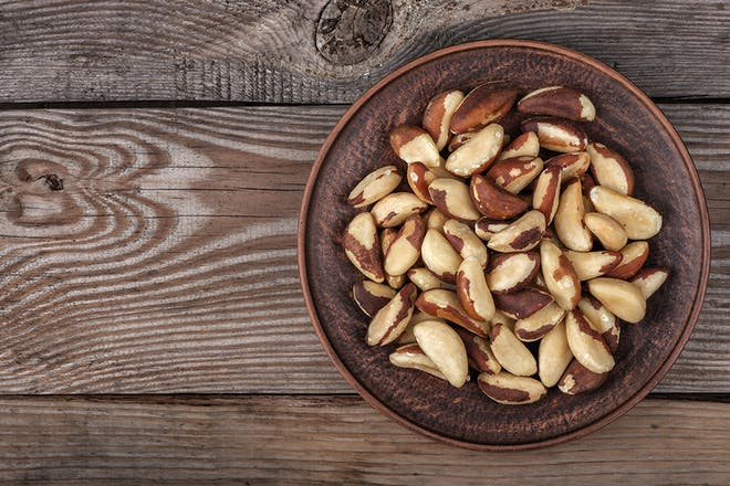 Brazil nuts in brown bowl on wooden background