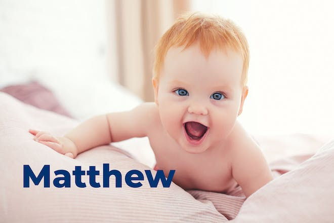 Baby with red hair laughing and trying to crawl. Name Matthew written in text