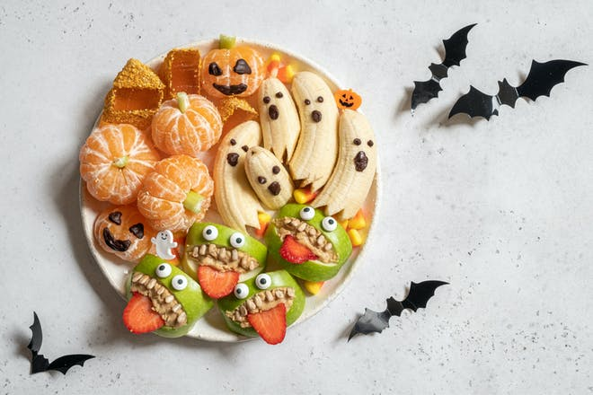 Bananas, apples and oranges on a plate decorated as monsters