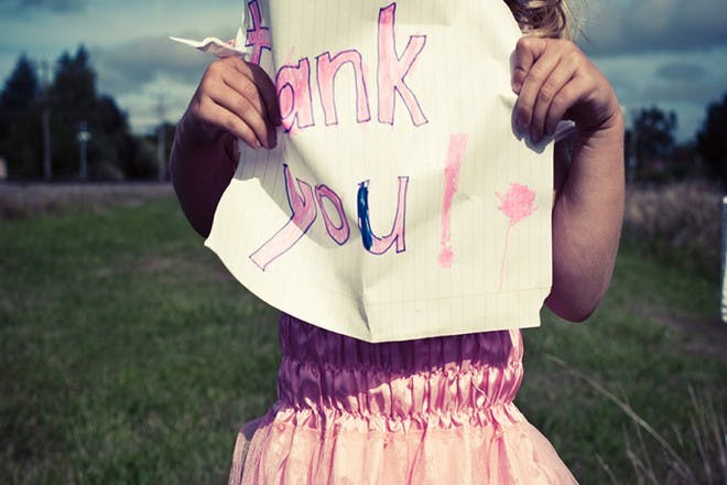 girl in field holding paper with thank you written on it