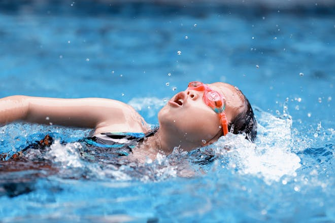 child swimming in a pool with goggles on