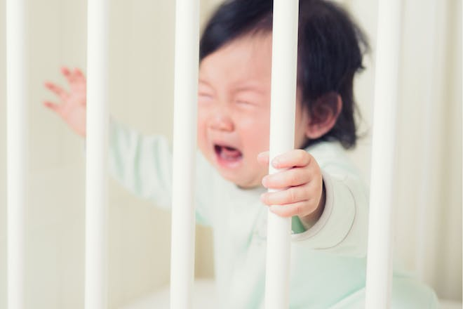 Baby crying holding bars of cot