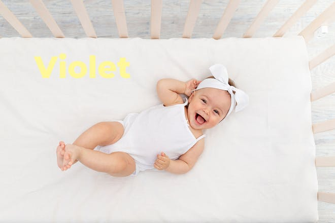 Baby in cot wearing headband. Name Violet written in text