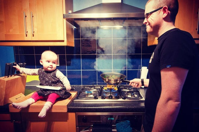 dad photographing baby daughter in kitchen