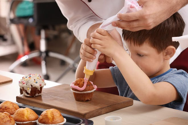young boy decorating cupcakes