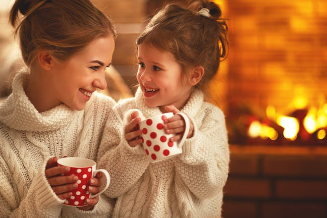 Mum and daughter drinking from mugs in front of fire
